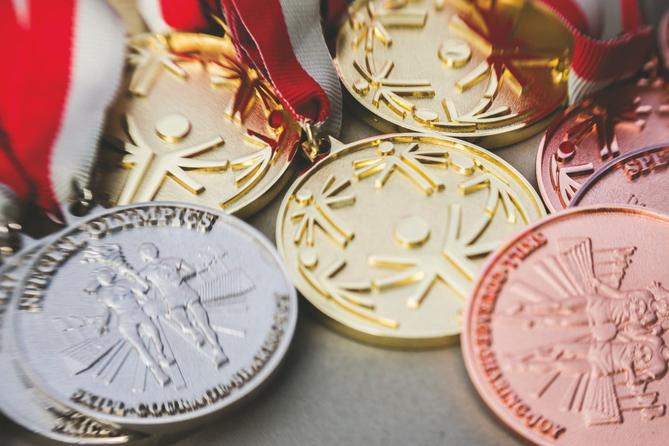 Group of silver, gold, and bronze medals laying down