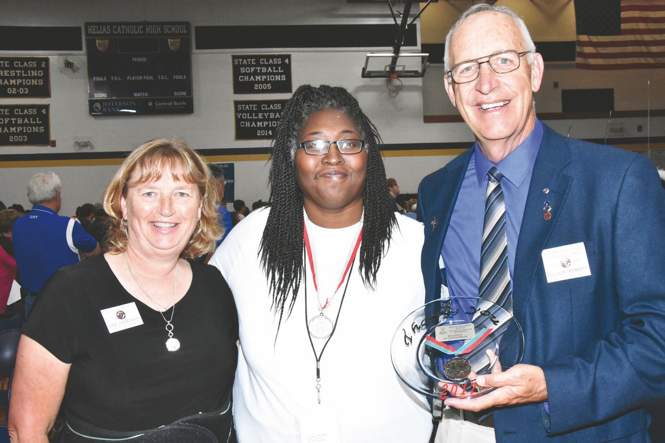 Athlete with medal around neck poses with volunteers holing a circular award