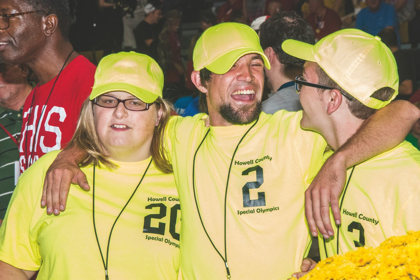 Three athletes from Howell County in bright yellow shirts smile at one another with arms around one another
