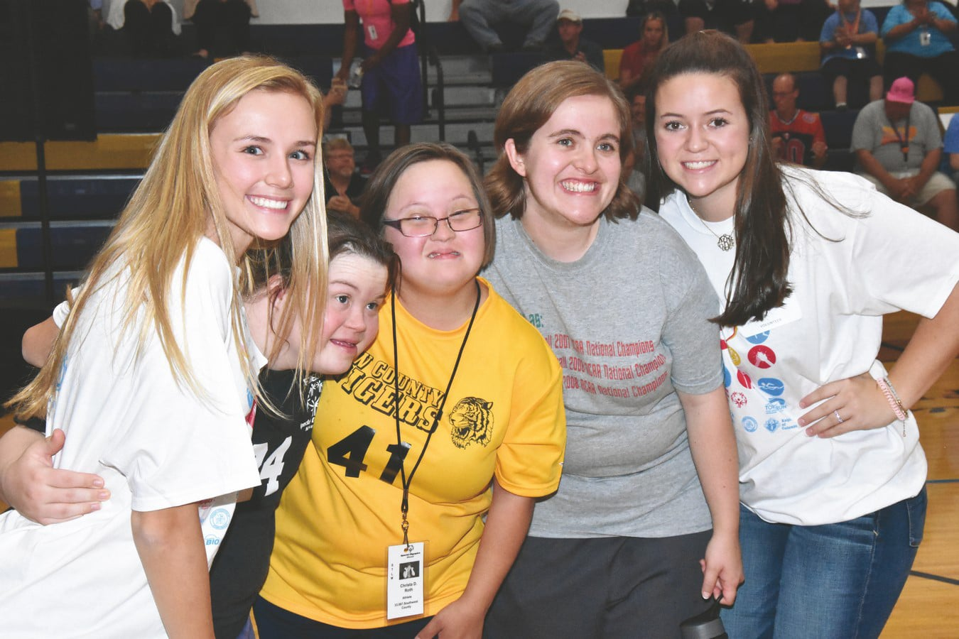 Athletes pose with volunteers while hugging and smiling at the camera