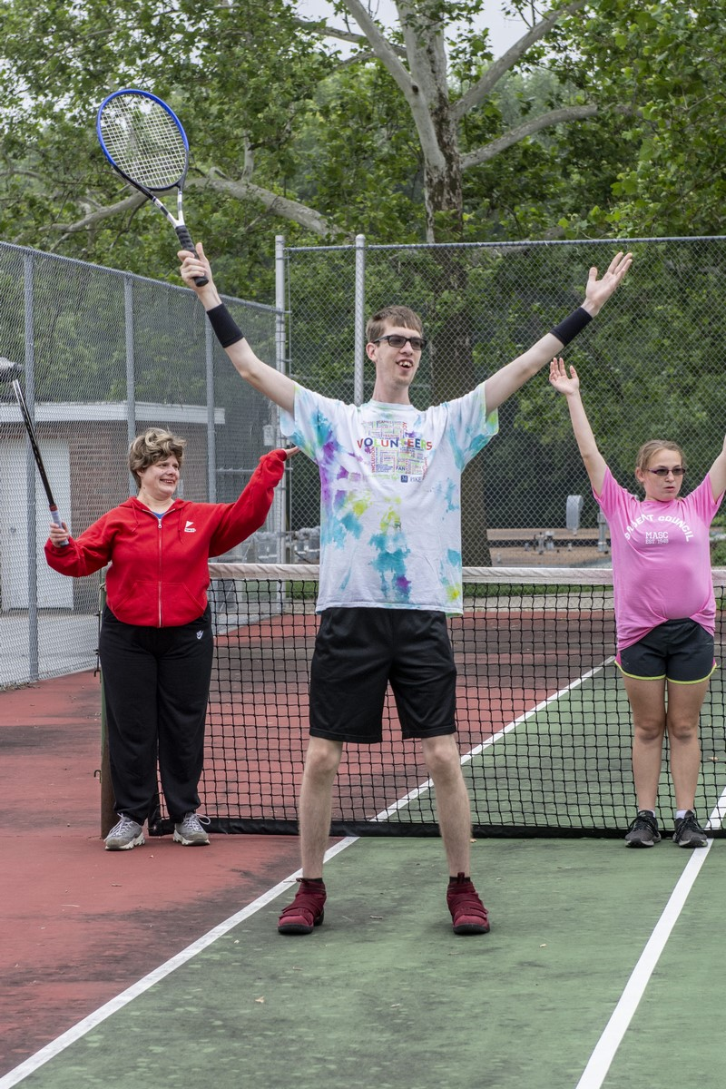 Three tennis athletes stand on a tennis court with their rackets raised high in the air