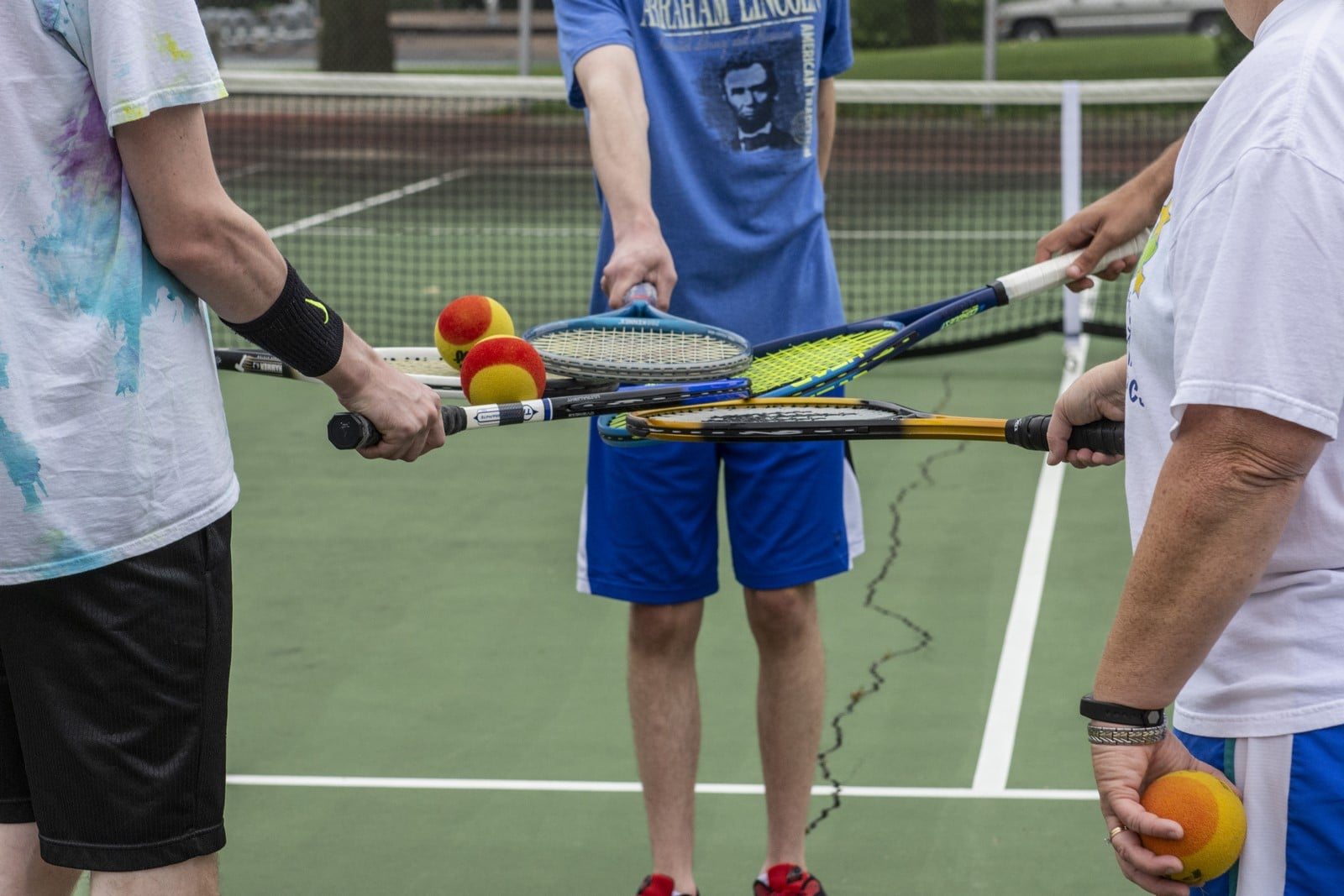 A tight photo of four tennis rackets all touching and overlapping in a circle
