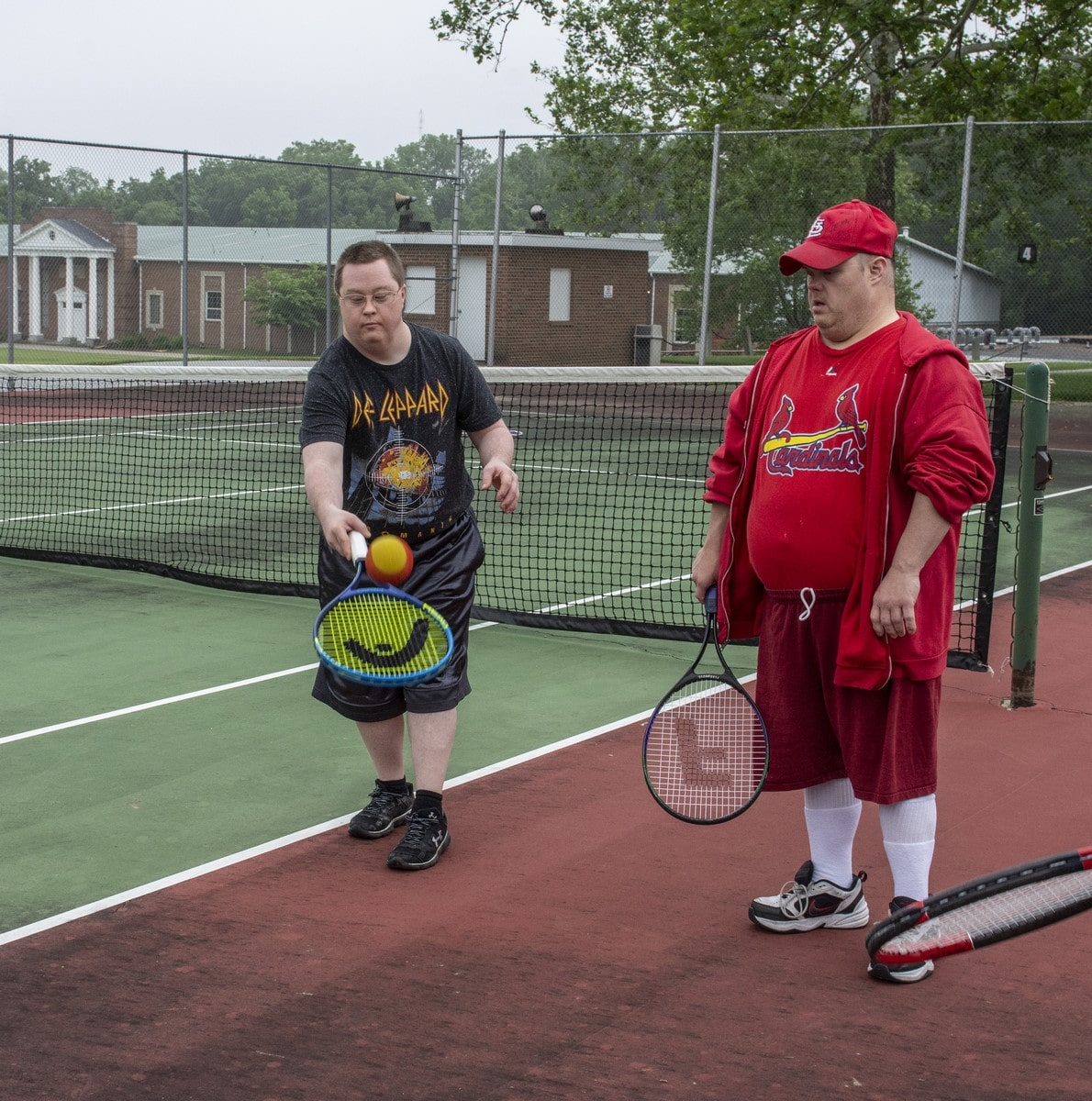 An athlete juggles a tennis ball on their racket while another athlete looks on