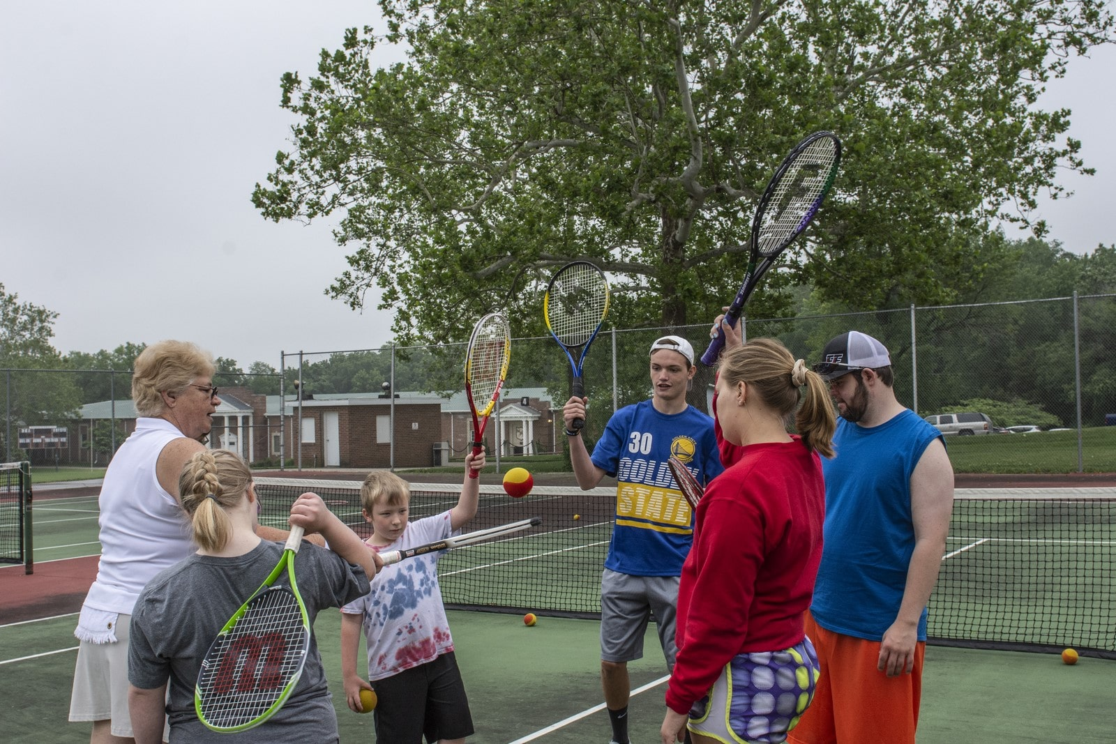 A group of athletes raise their tennis rackets into the air
