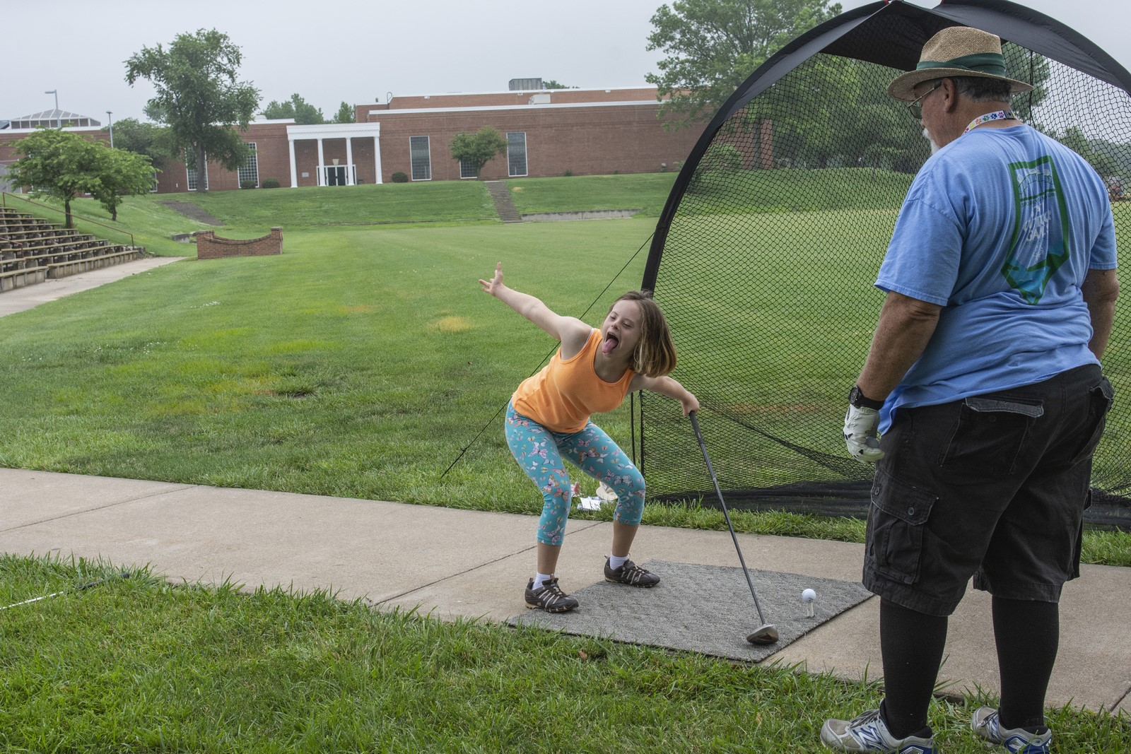 An athlete holding a golf club and smiles and makes a face at other athletes as a coach looks on