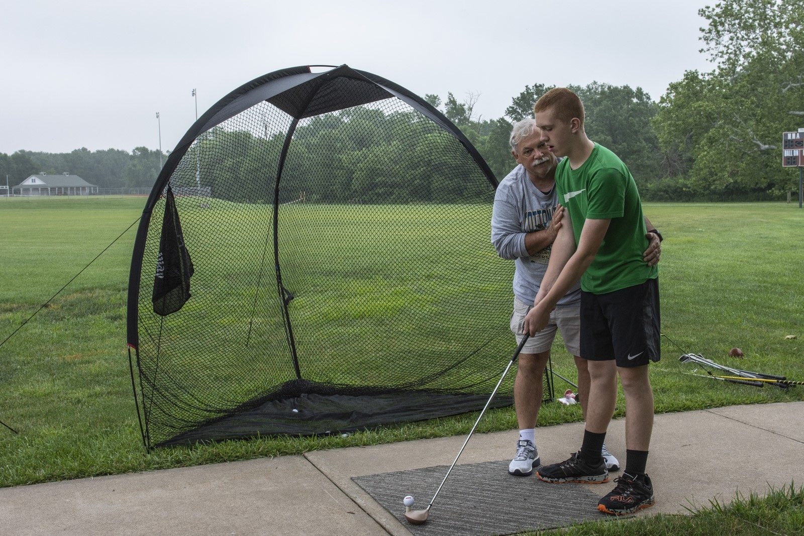 A coach shows an athlete how to stand and swing a golf club