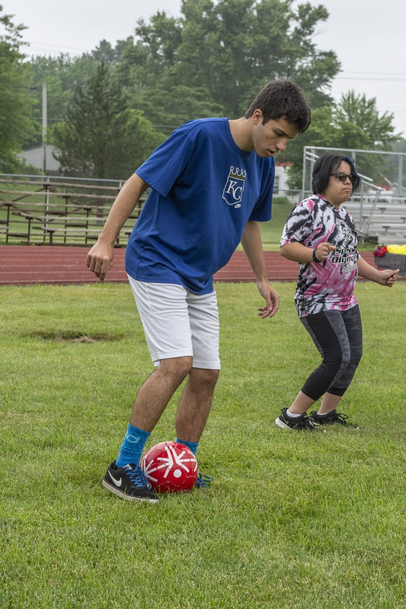 An athlete looks down at the soccer ball as they dribble