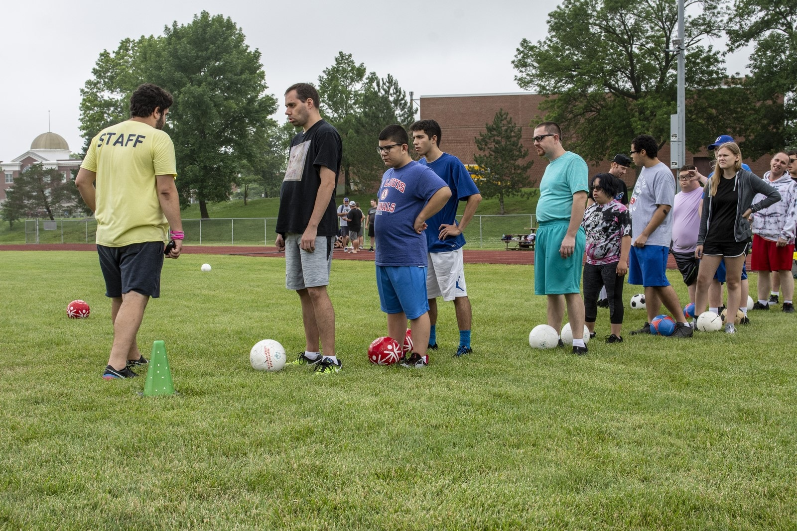 A line of athletes stand with soccer balls at their feet listening to the volunteer's suggestions
