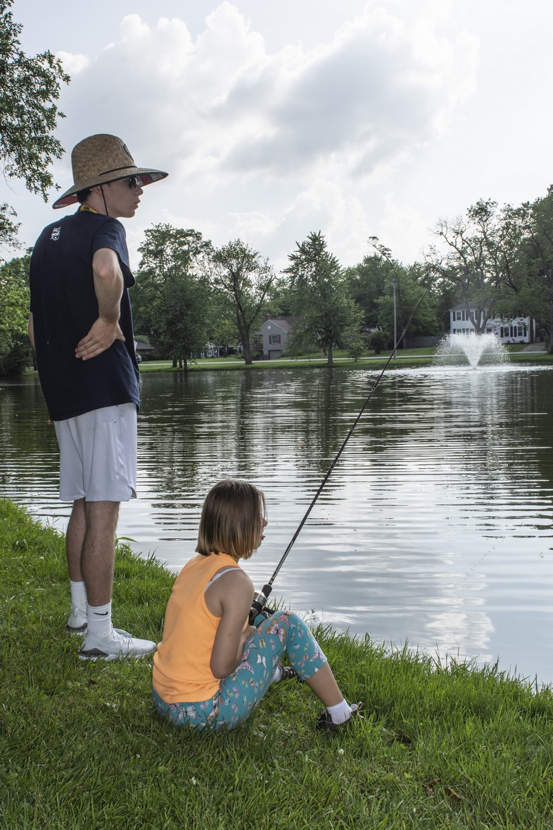 An athlete sits in the grass and fishes in a lake while a volunteer looks on
