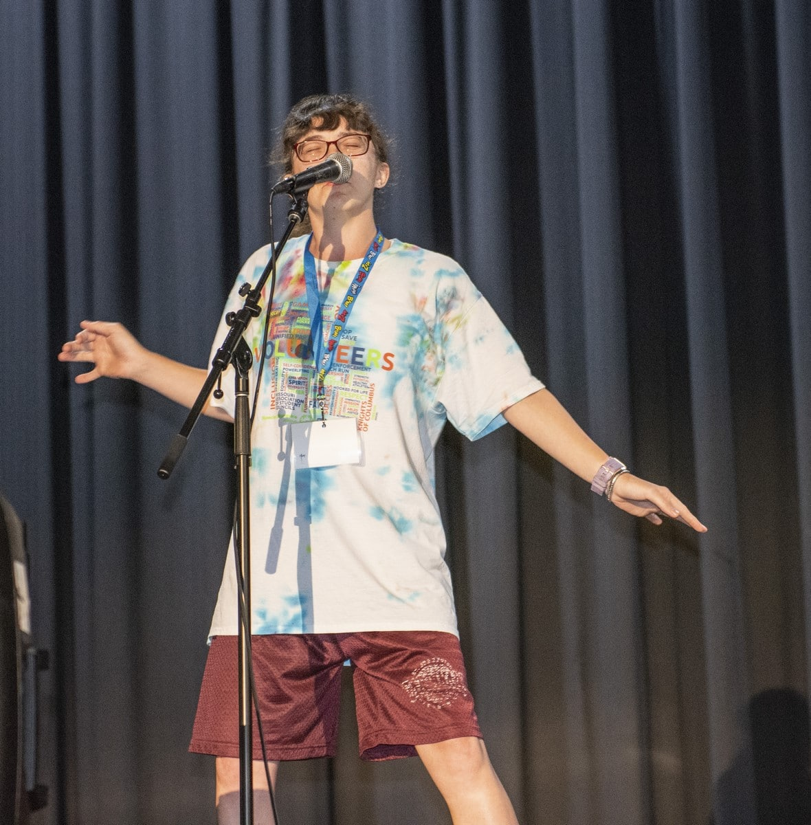 An athlete sings on a stage during a talent show