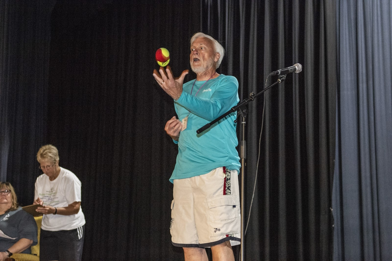 A volunteer juggles on a stage during a talent show