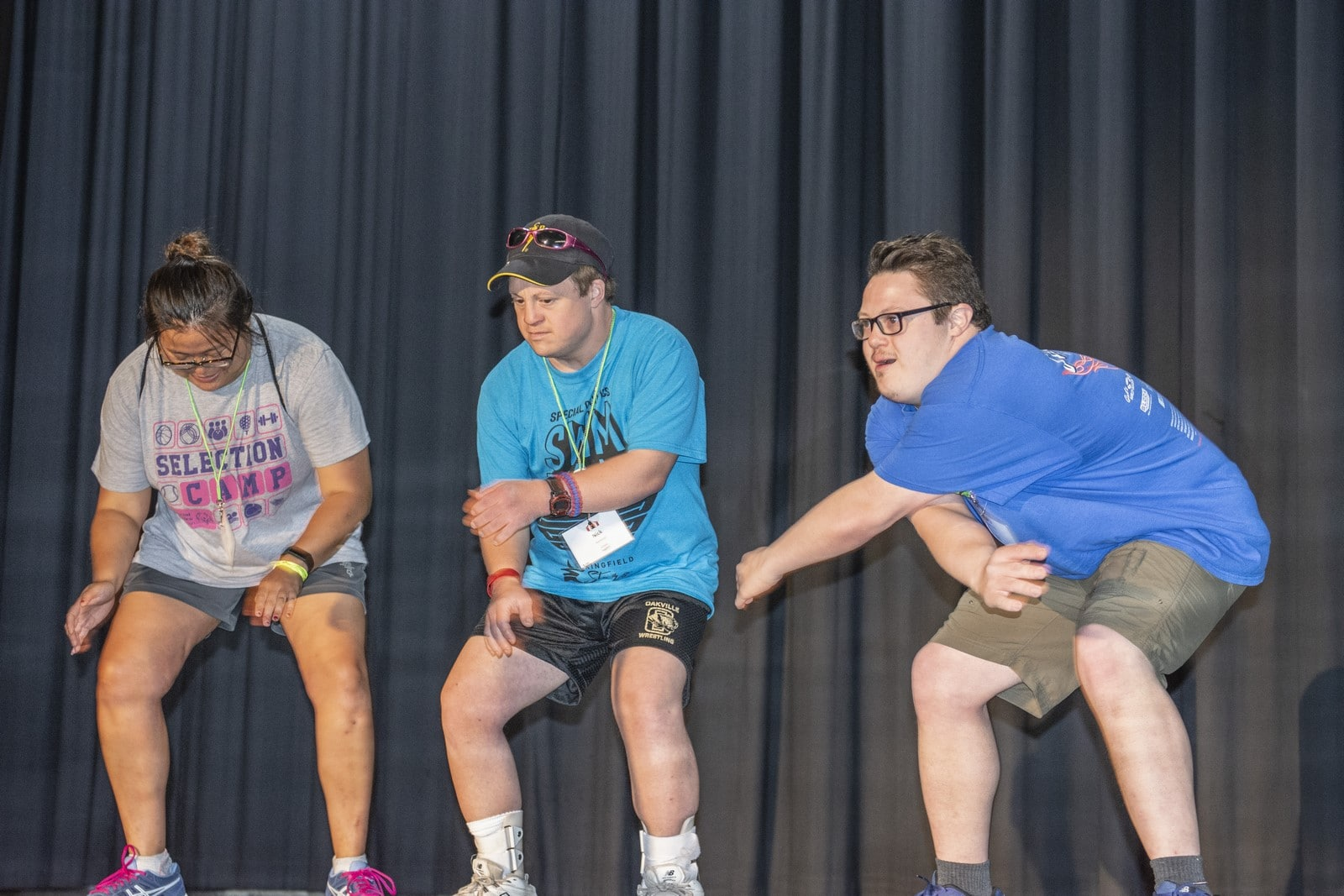 Three athletes perform on a stage during a talent show