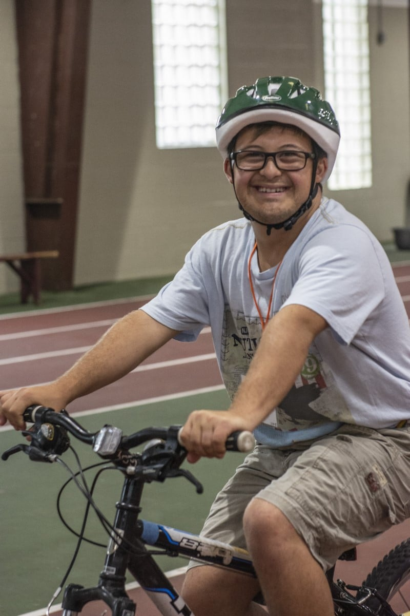 An athlete rides a bike with a smile as they pass by and look directly at the camera