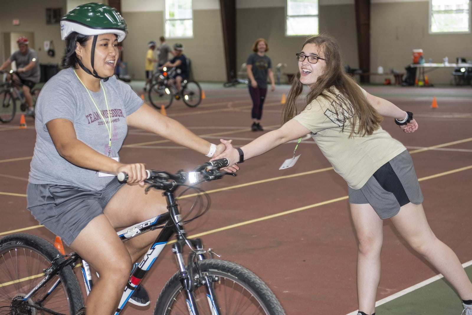 An athlete rides a bike while a volunteer gives them a high-five