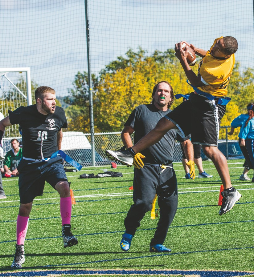 An athlete jumps high into the air to catch the football while two defenders look on
