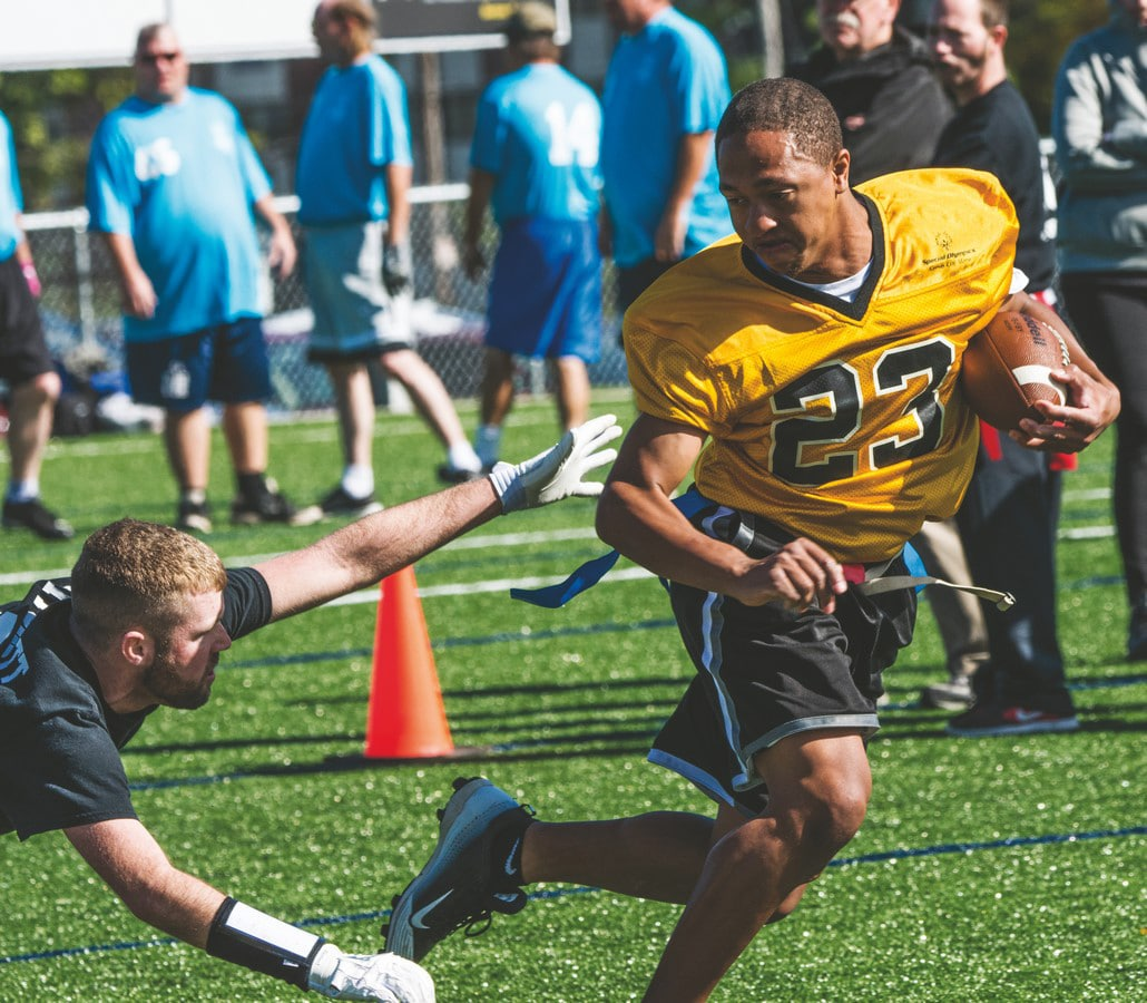 An athlete carries a football in their left arm while avoiding the outreaching grasp of a defender trying to grab their flag