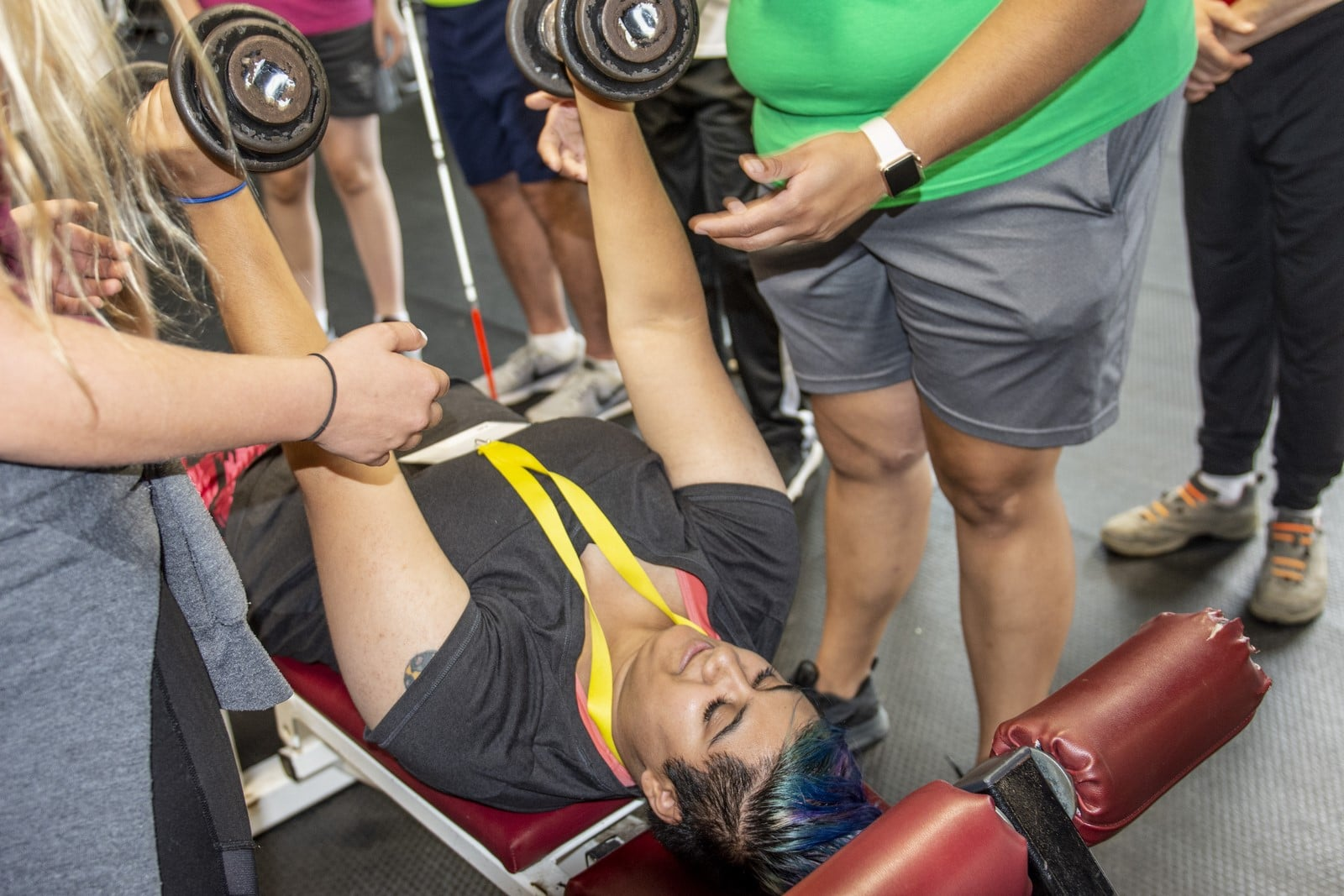 An athlete lies on a bench and presses weights to the sky while others look on