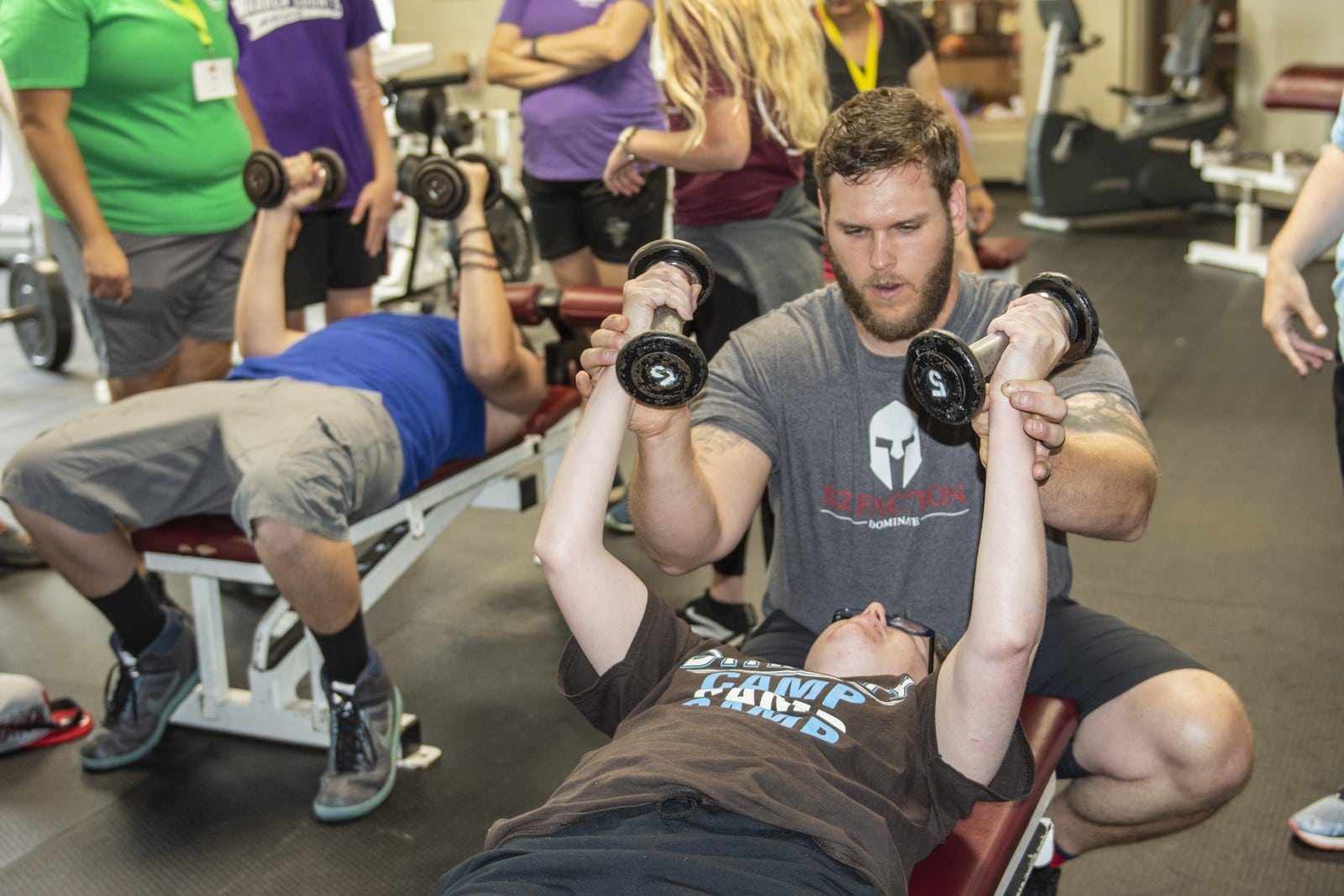 An athlete lies on a bench pressing weights to the sky with the help of a coach spotting them
