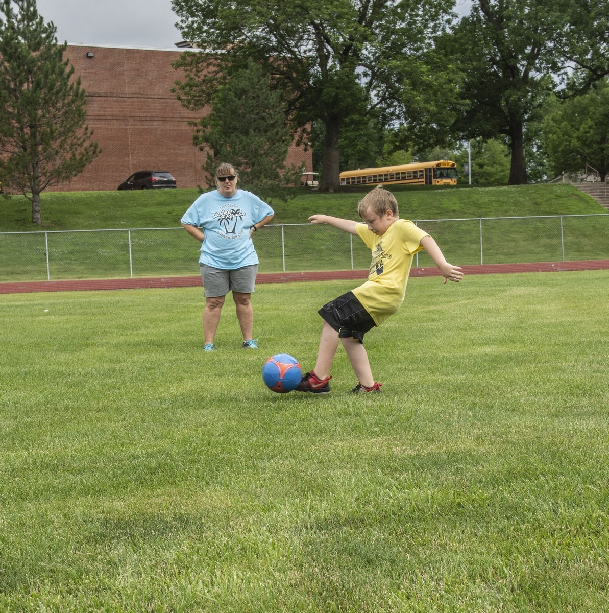 A young athlete strikes a soccer ball with their foot