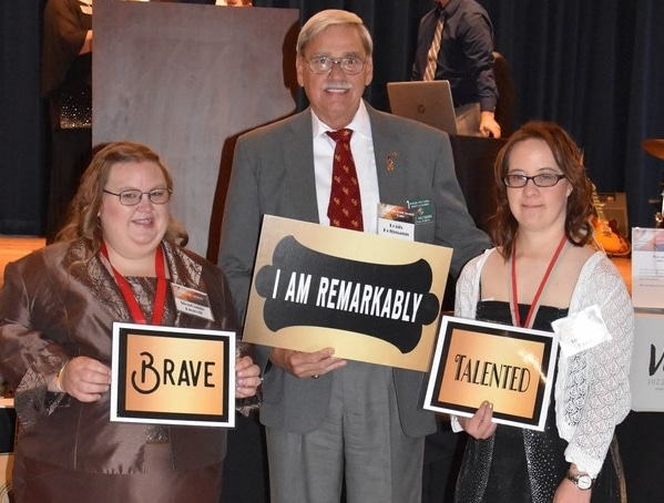 """Two athletes and a volunteer pose for a photo while holding signs that say """"I am remarkably,"""" """"Brave,"""" and """"Talented"""""""