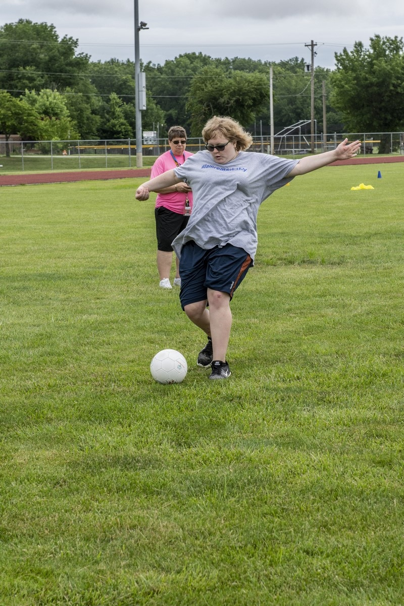 An athlete stretches out their arms as they prepare to kick a soccer ball