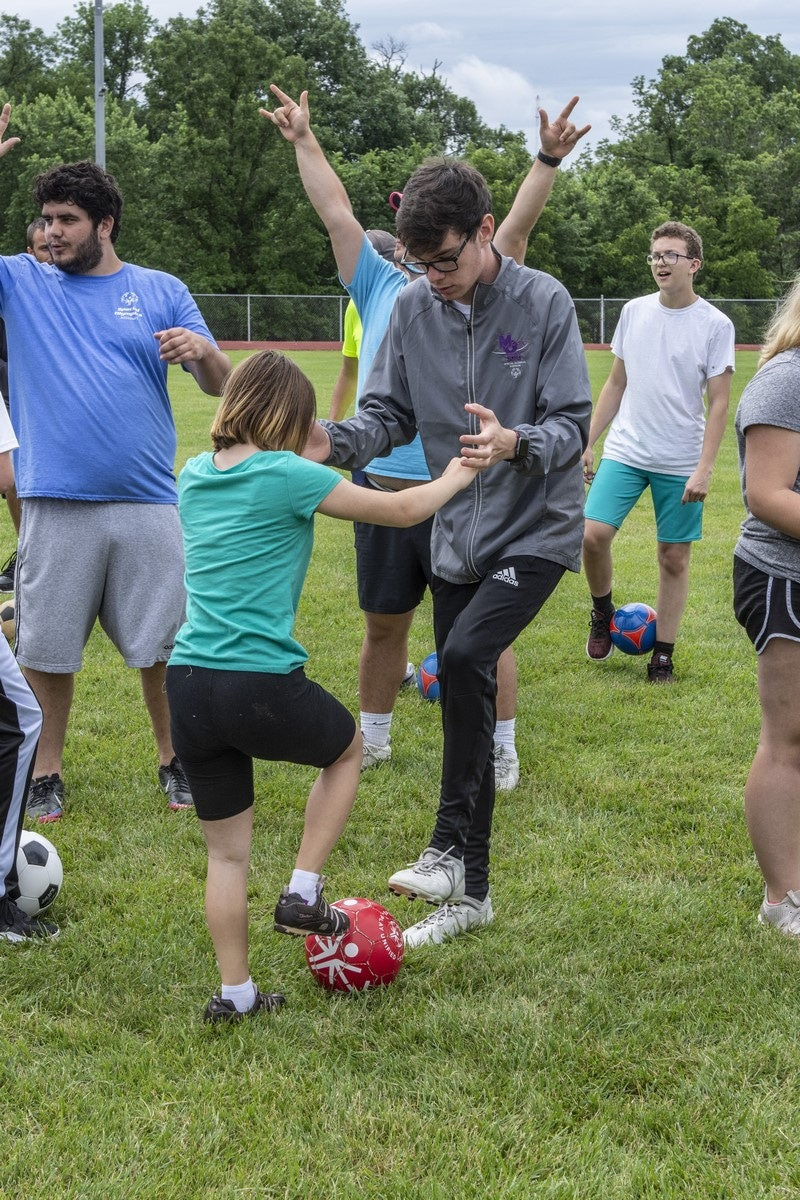 A volunteer holds hands with an athlete to better balance themselves as they practice tapping their toes on a soccer ball