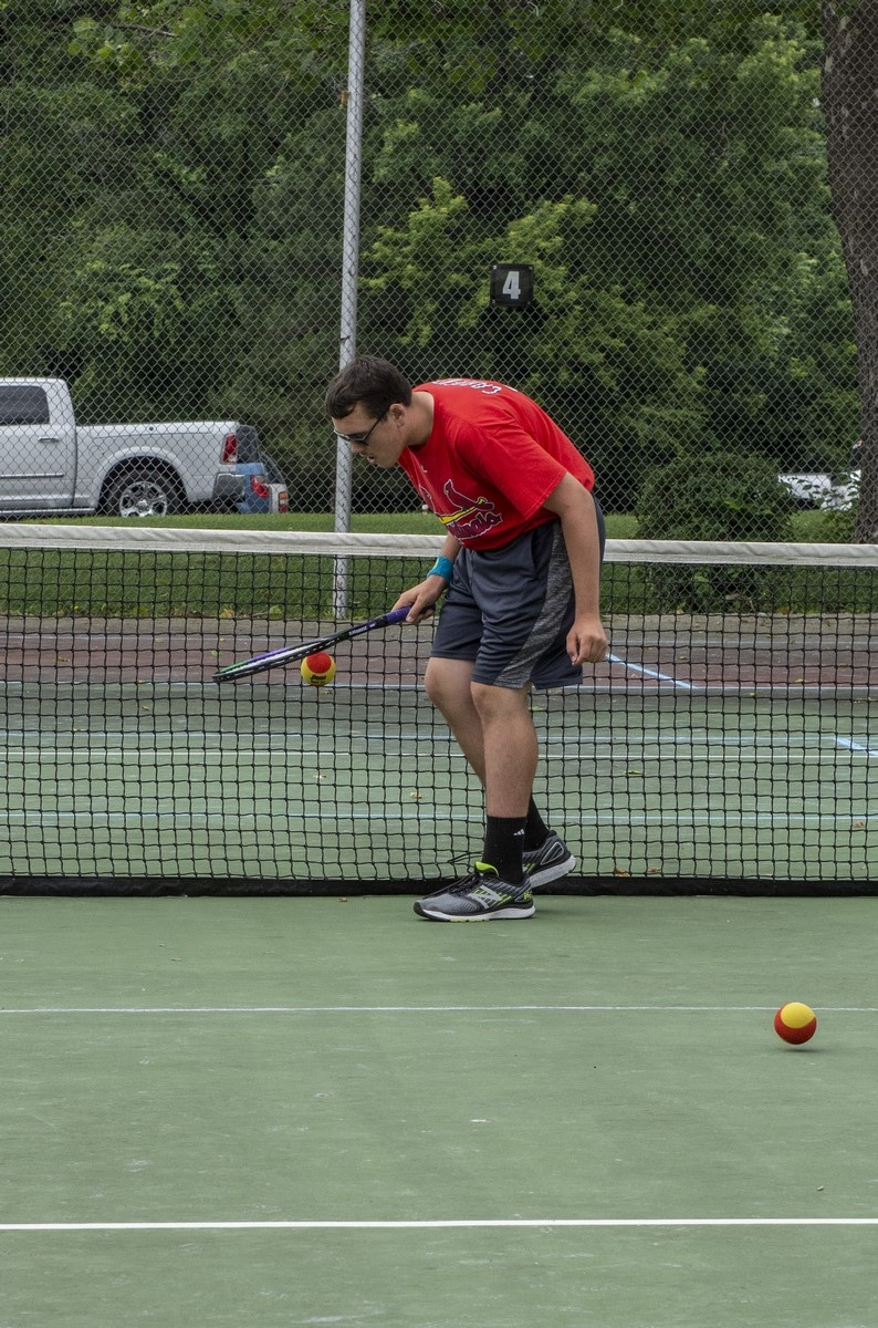 An athlete bends over and dribbles a tennis ball with their racket on the court