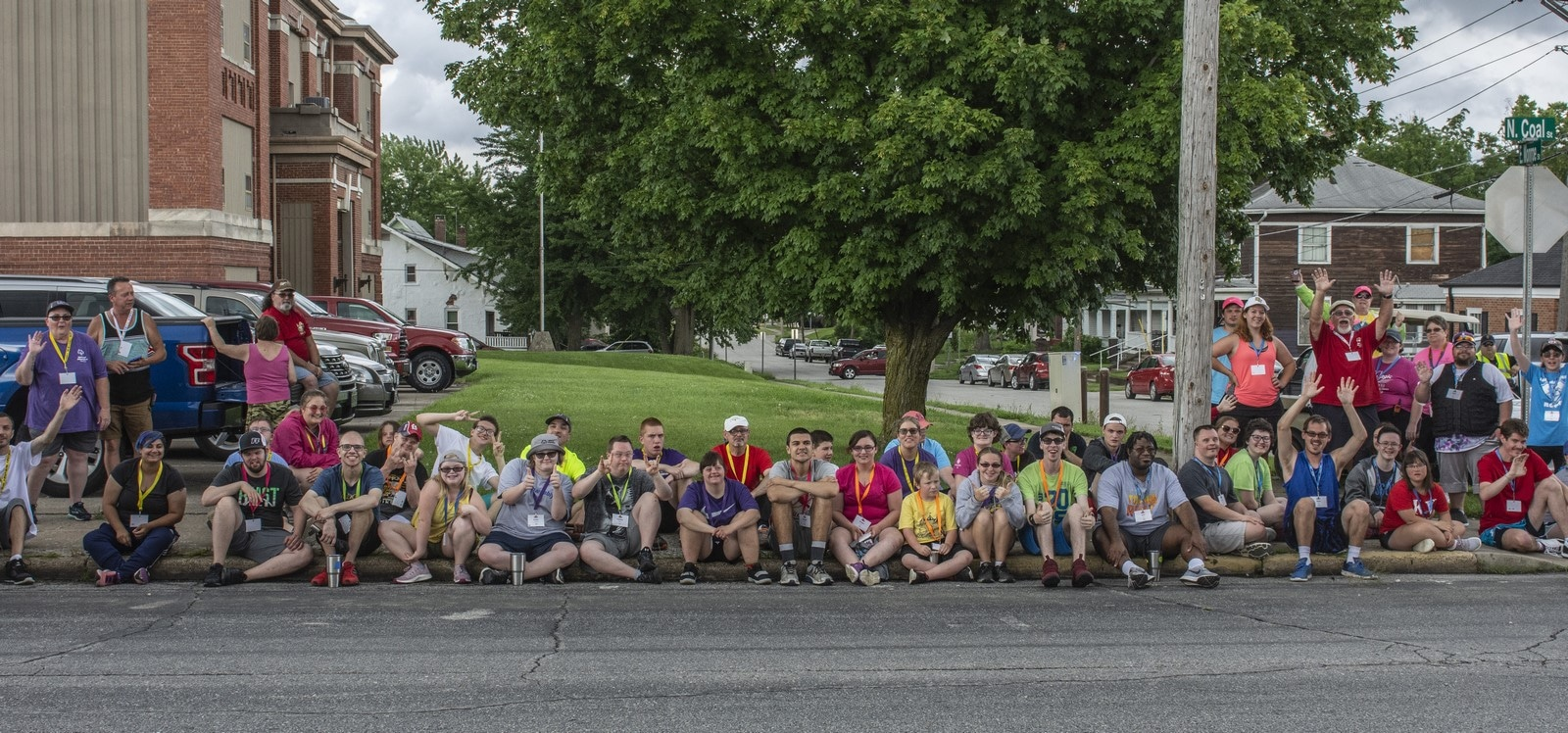 A large group of more than 75 athletes and volunteers sit on a curb and watch a parade
