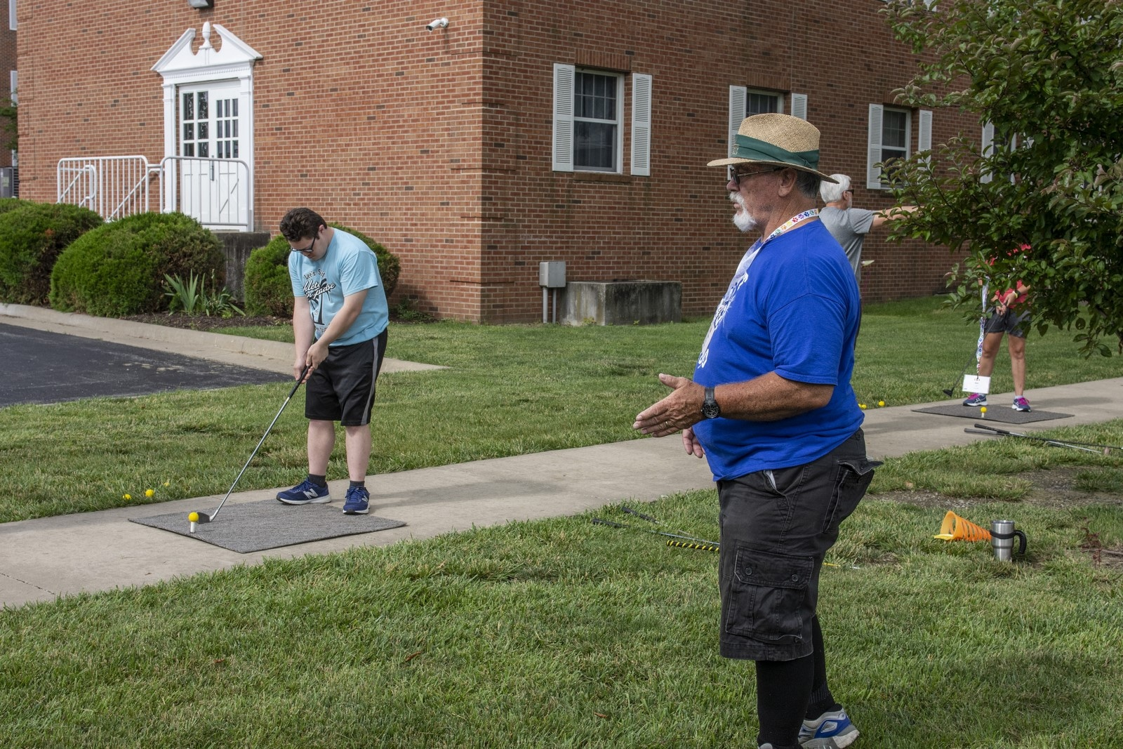 An athlete practices their golf swing off a practice mat while a coach looks on