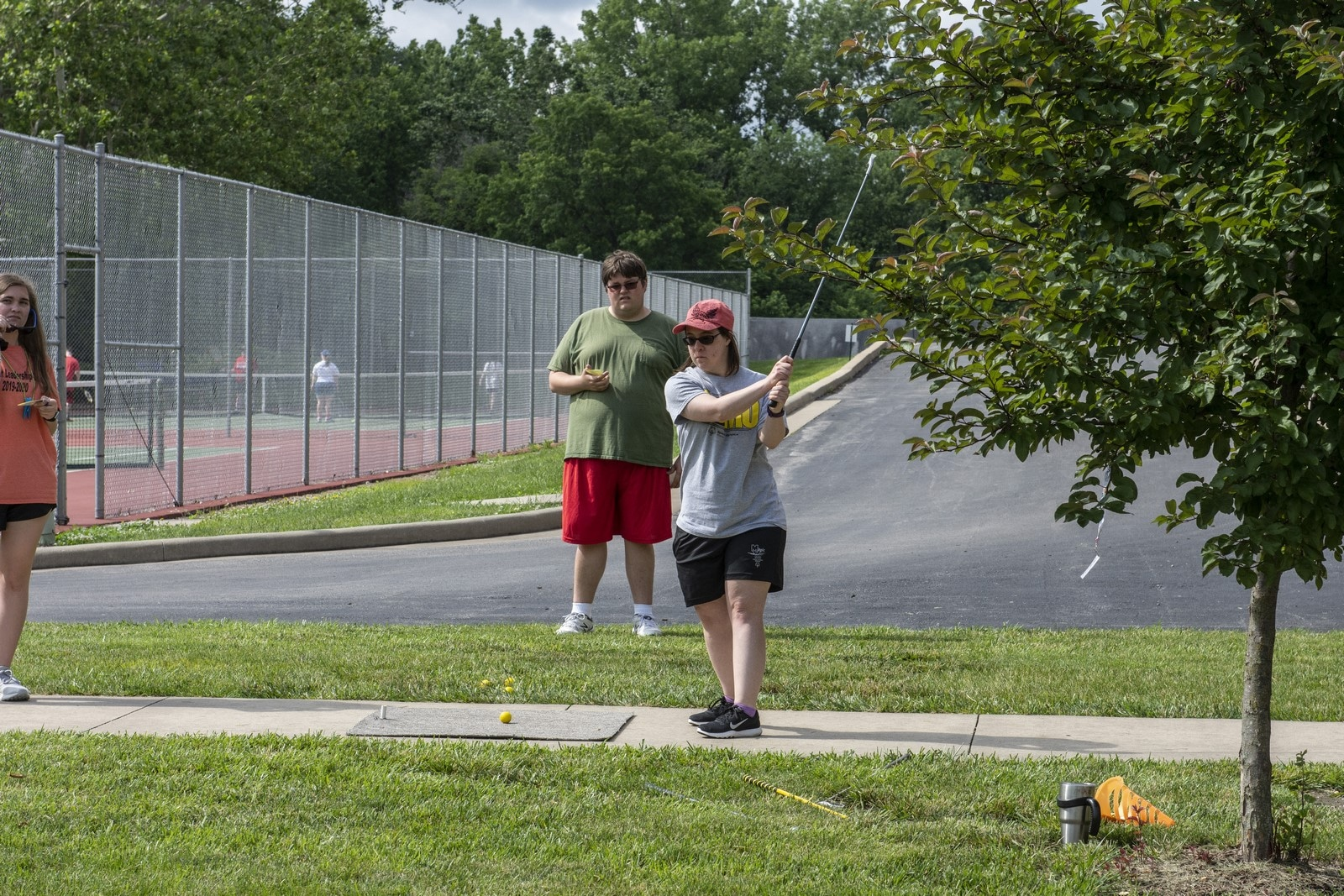 An athlete practices their golf swing off a practice pad while another athlete watches from behind