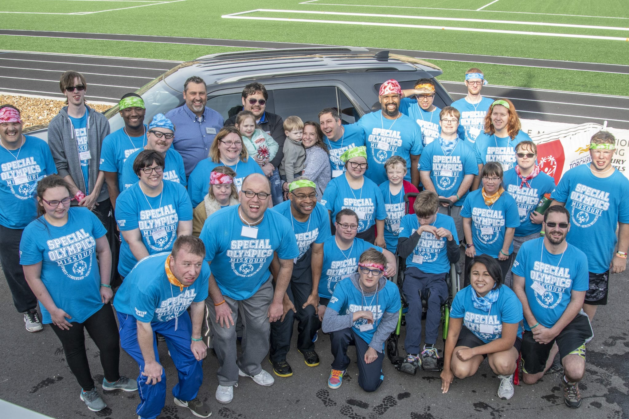 A group of two dozen athletes pose for a photo with car raffle winners