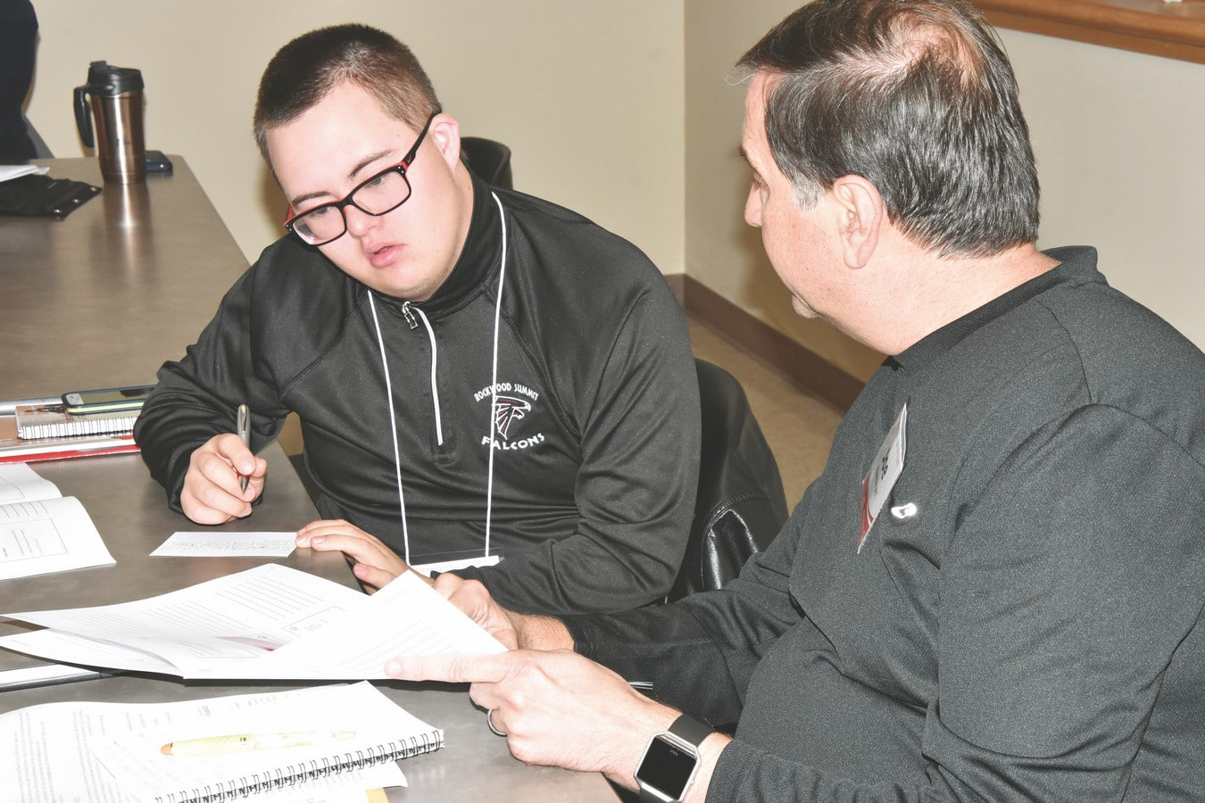 A mentor shows an athlete-leader notes during an Athlete Leadership class