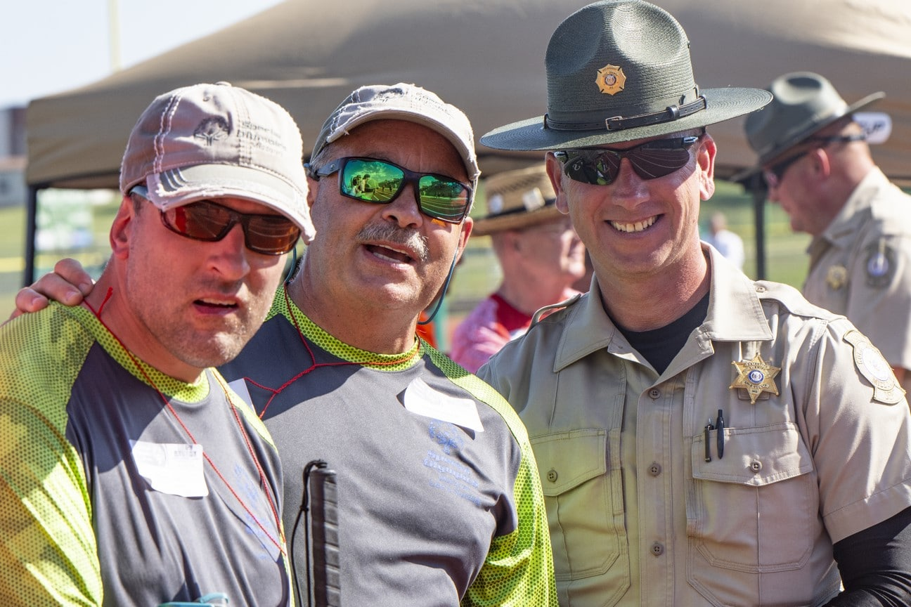 Athlete, Unified Partner, and police offer smile and pose together looking at the camera