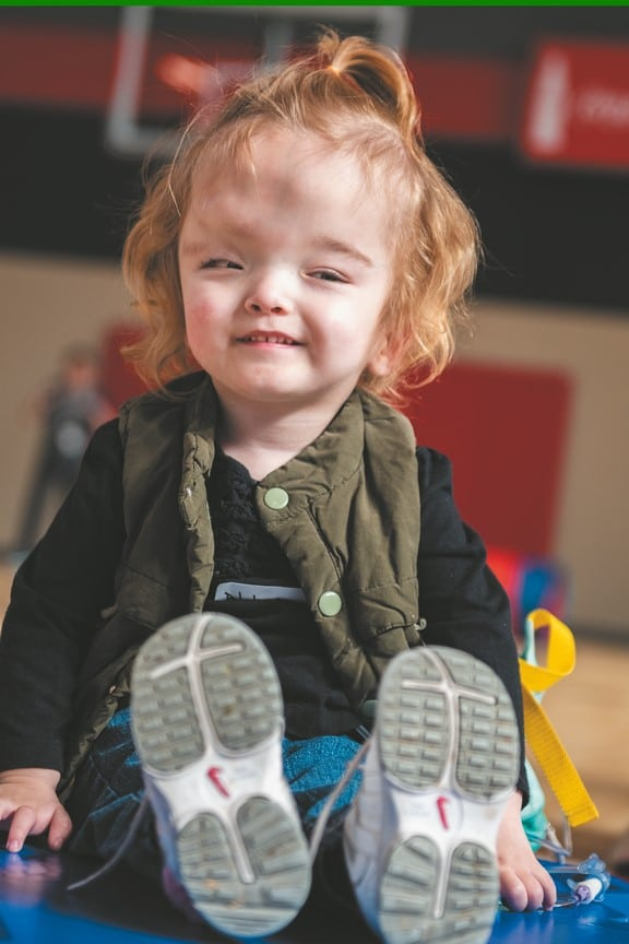 A Young Athlete sits on a scooter board and smiles at the camera