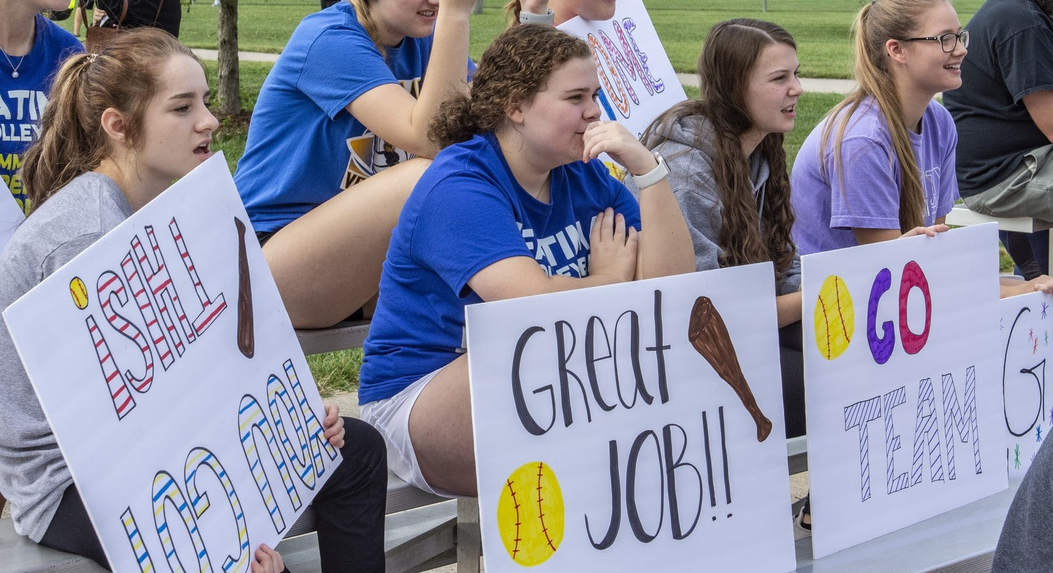 Volunteers sit on bleachers with encouraging posters watching a softball game
