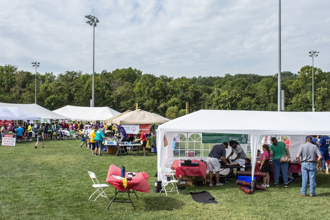 Four large tents sit in a field between softball fields while athletes receive health screenings in them