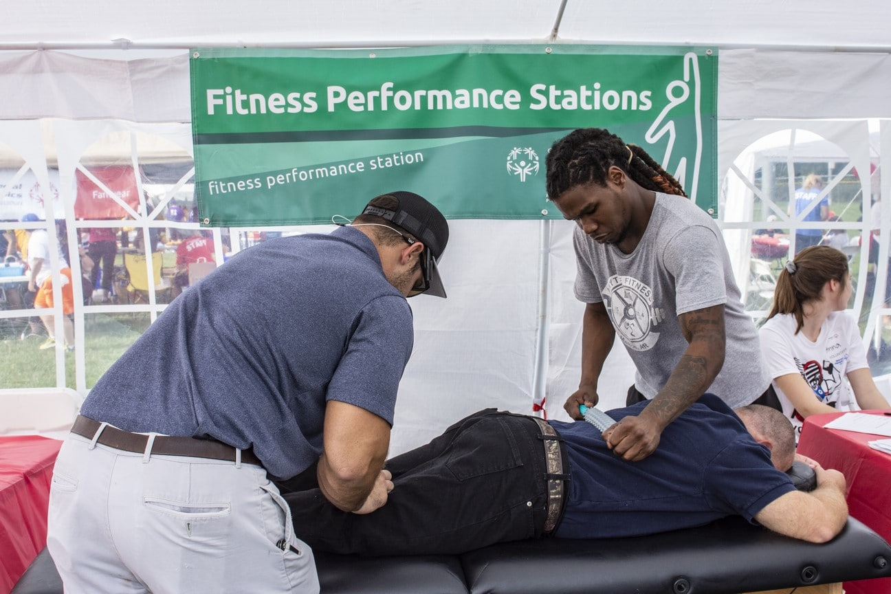 An athlete lies face down on a table while two volunteers massage their back and legs