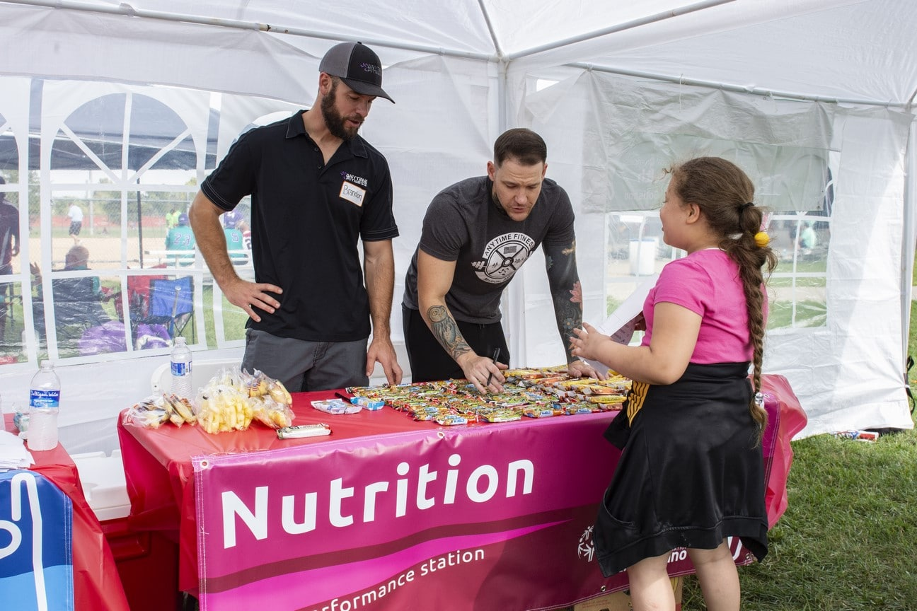 Two volunteers talk to an athlete at a nutrition station and hand them a granola bar