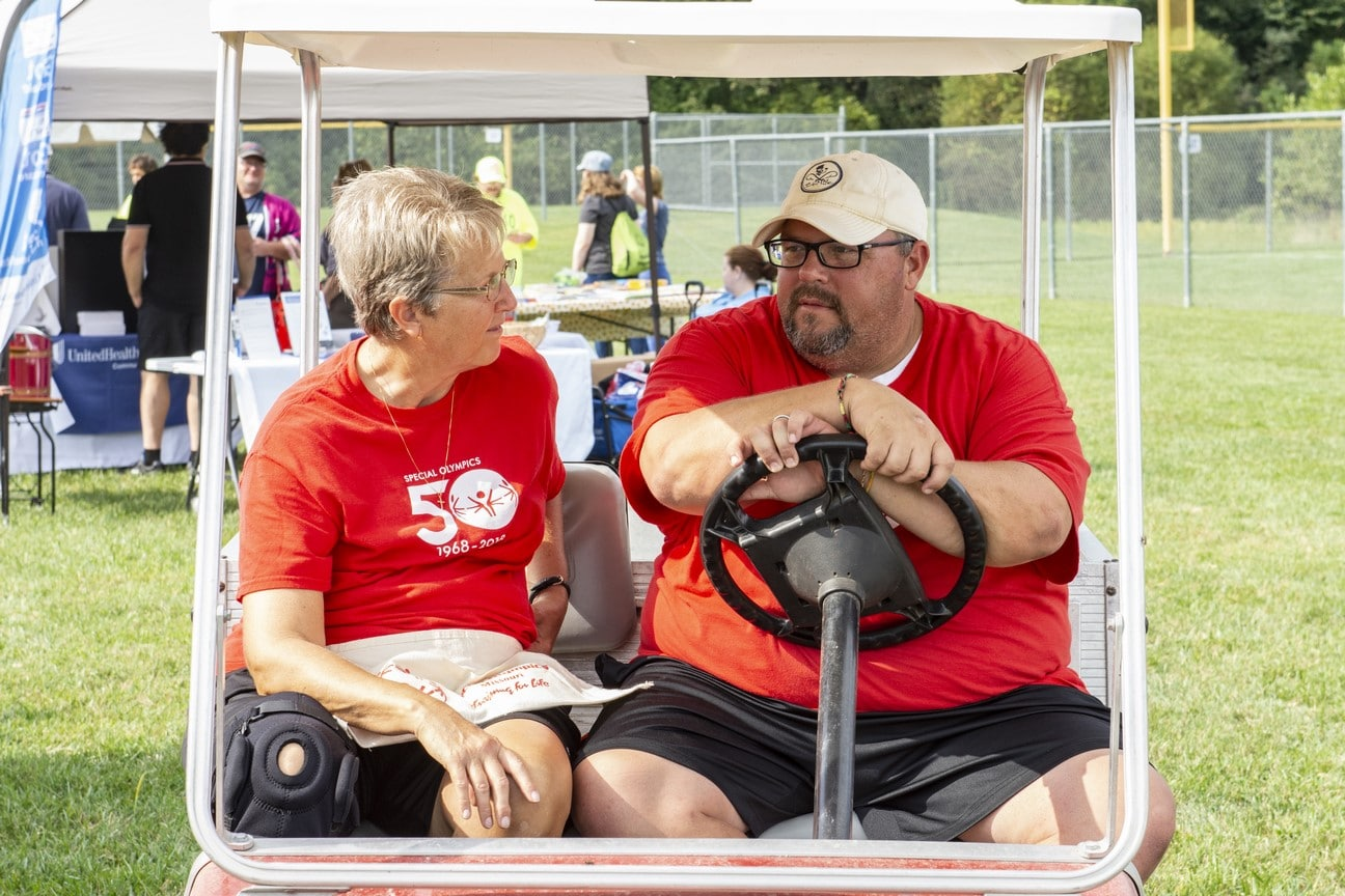 Two SOMO staff members sit on a golf cart and talk