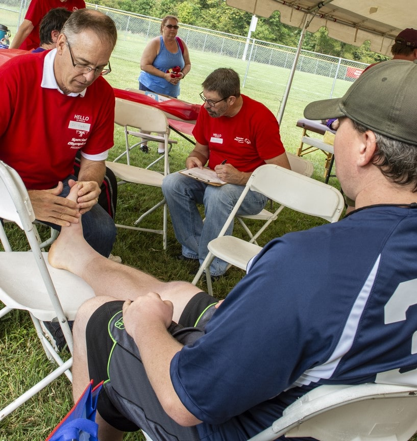 An athlete sits in a chair while a doctor inspects their foot