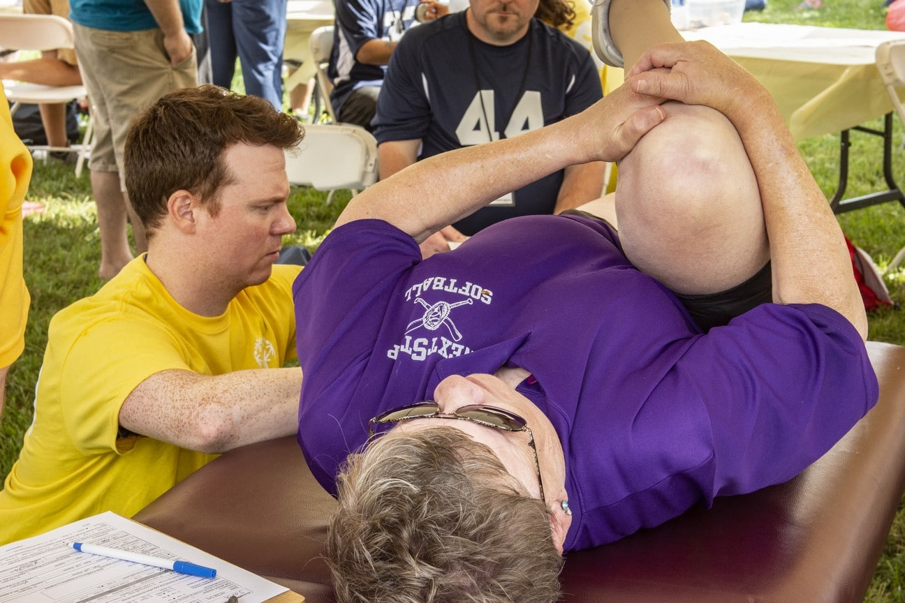 An athlete lies on a table, holding their knee to their chest while a health professional measures their flexibilityl