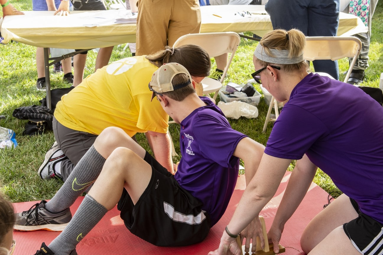 An athlete sits on the ground while a health professional measures their flexibility