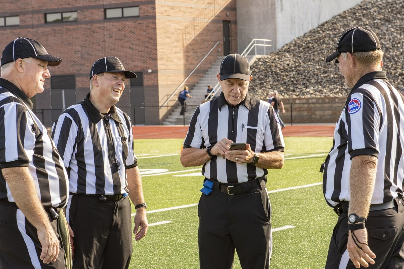 Four referees gather on the field