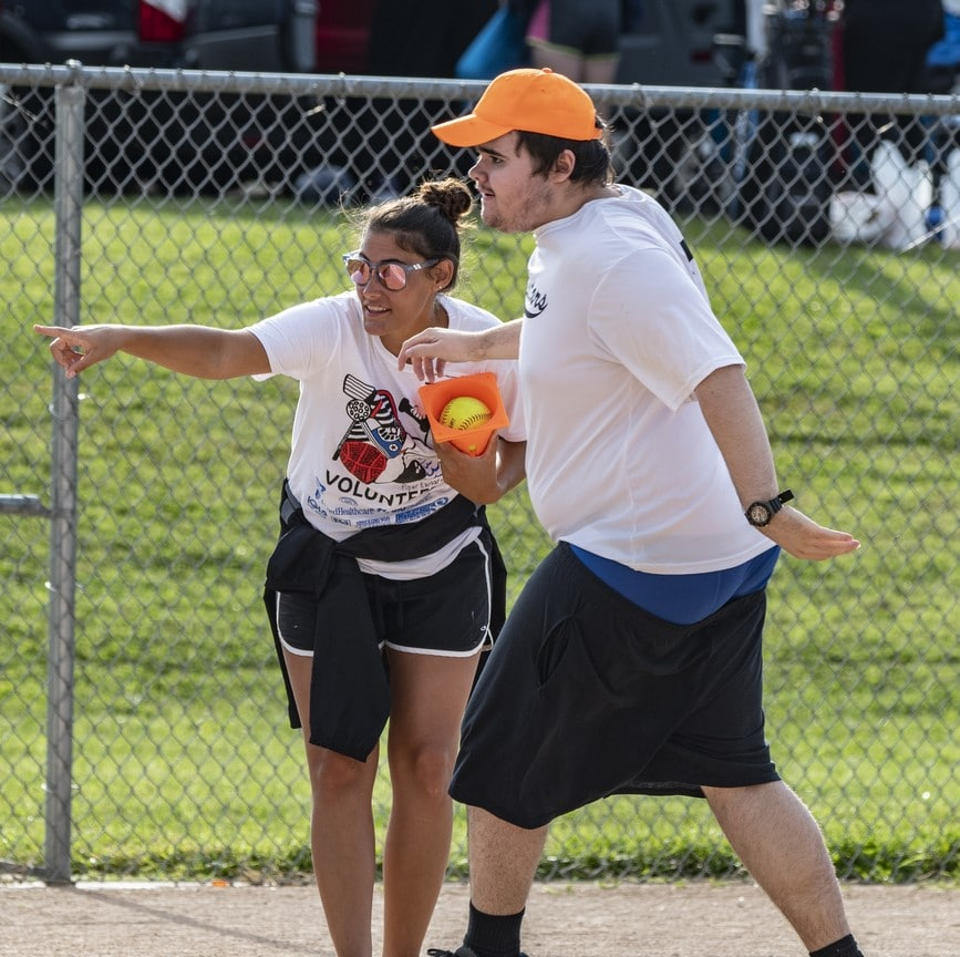 Volunteer points to side as athlete runs the bases