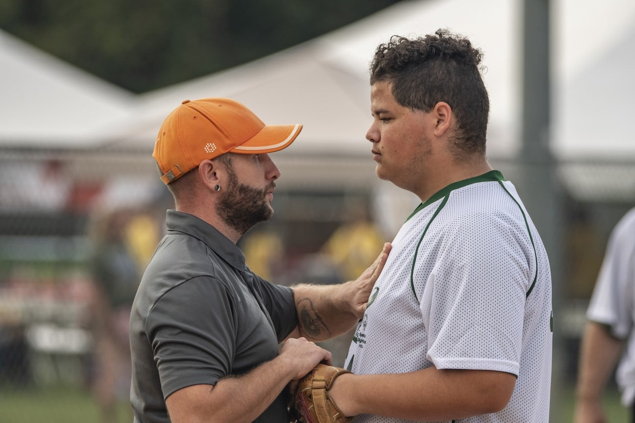 Coach faces athlete and places hand on their heart and softball glove