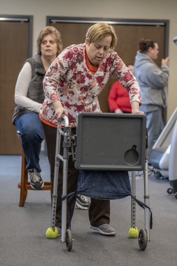An athlete using a walker works out in the fitness center of the Training for Life Campus