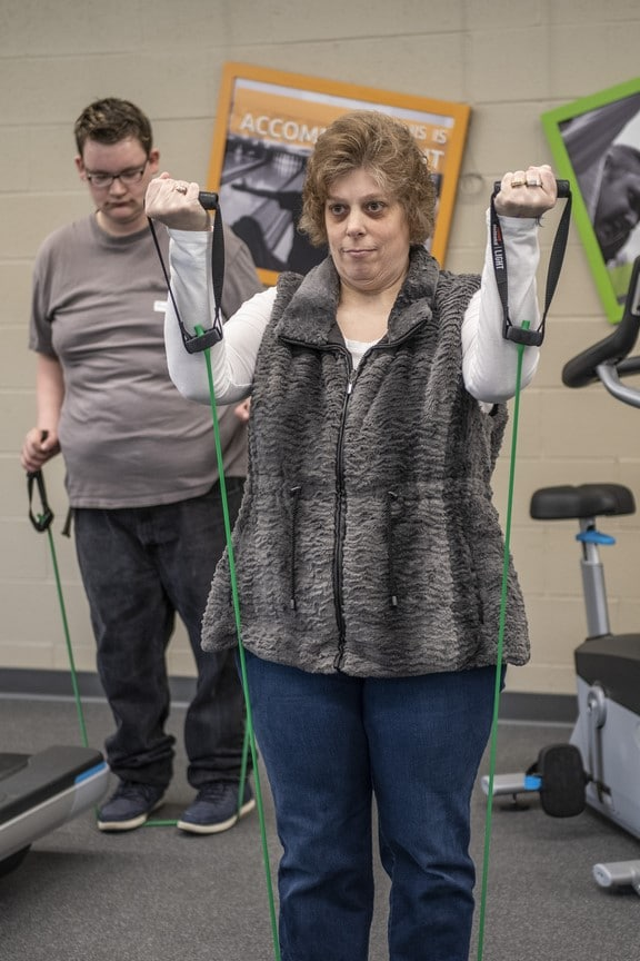 Two athletes use workout bands in the fitness center at the Training for Life Campus