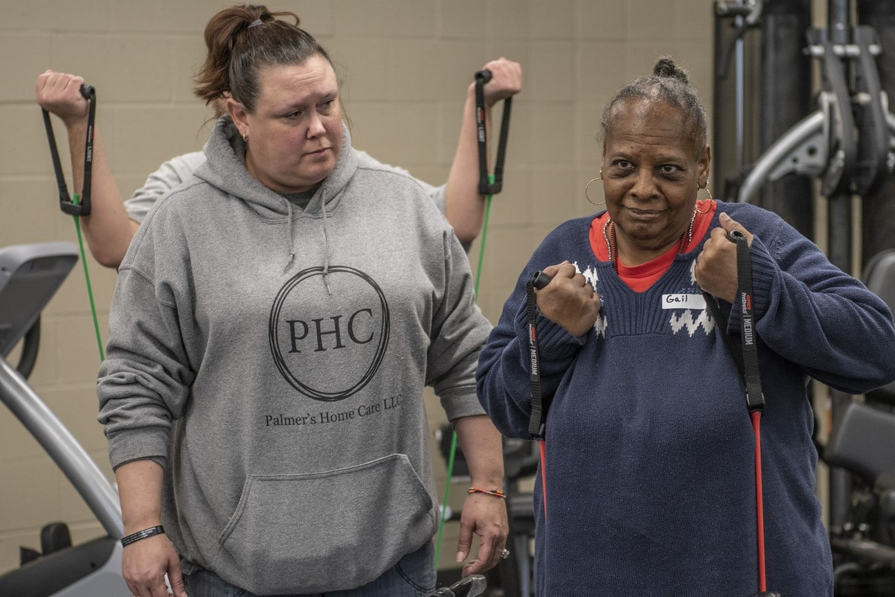 An athlete uses workout bands while a volunteer looks on