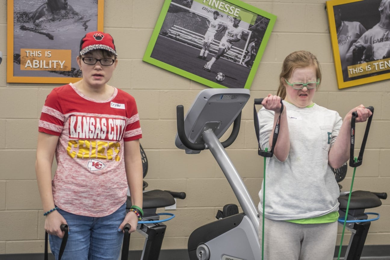 Two athletes use workout bands in the fitness center of the Training for Life Campus