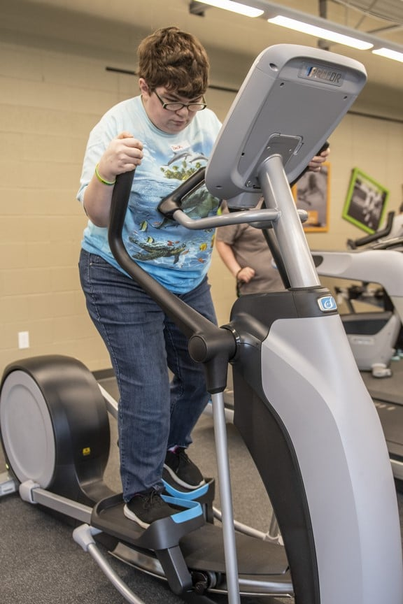 An athlete watches their feet while they workout on an elliptical at the Training for Life Campus